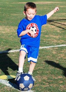 Young boy kicking soccer ball
