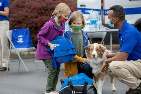 Two masked girls and their dog with a masked emergency services worker