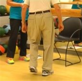 Older man balancing on one foot in exercise studio.