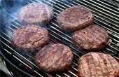 Photo of charcoal grill with five grill marked, smoking hamburgers.