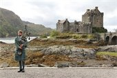 Scottish man playing bagpipes in front of Scottish castle.