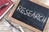 """Notebook, pen, eye glasses, and """"Research"""" written on blackboard."""