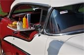 Photo of old classic red/white car with window tray filled with drive-in diner food.
