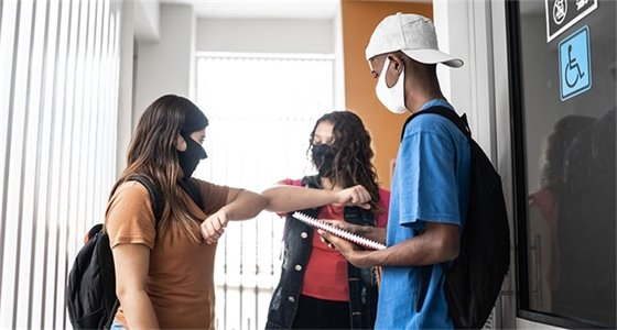 Three masked adolescents in a hallway, two are bumping elbows