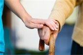 Caregiver's hand on older adult hand.