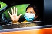 Woman driving orange car, wearing a mask and waving.