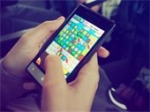 Person playing online game on smart phone.