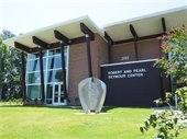 """Photo of the front of the """"Robert & Pearl Seymour Center"""" showing the new addition & art installation."""