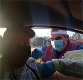 Photo of person getting vaccine from EMT