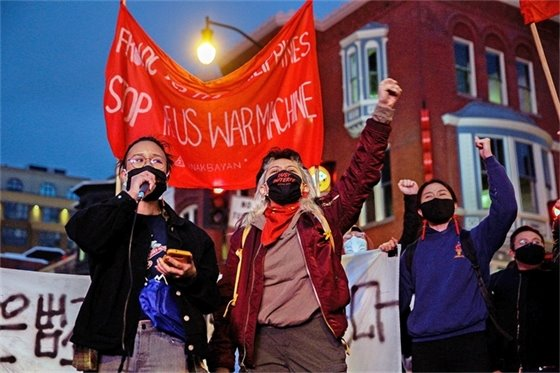 Image of masked protesters with fists in the air.
