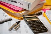 Image of Income Tax manual, calculator, calendar, financial spreadsheet and open ink pen.