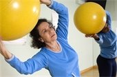 Older Hispanic woman exercising with an exercise ball.