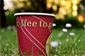 """Paper """"Coffee to Go"""" cup outside on grass."""