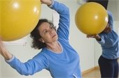 Older Latina woman exercising with large yellow exercise ball.