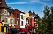 Washington, DC, neighborhood with colorful buildings, businesses, diverse national flags and murals.