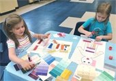 Pre-K Learn and Play: Two children decorating self portraits from National Coloring Day