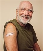 Older white man with sleeve rolled up and band-aid on his arm.