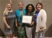 Janice Tyler, Terry Colville, Cydnee Sims, and Myra Austin holding NCOA-NISC 2018 Program of Excellence award.