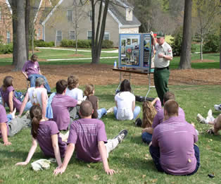 Kids sitting on the grass at Envirothon presentation