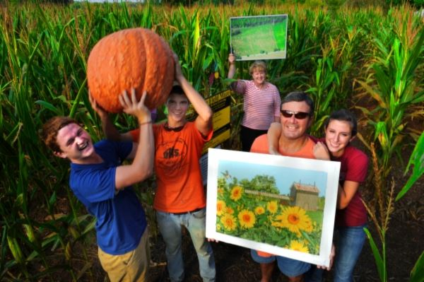 Family holding large pumpkin at Corn Maze