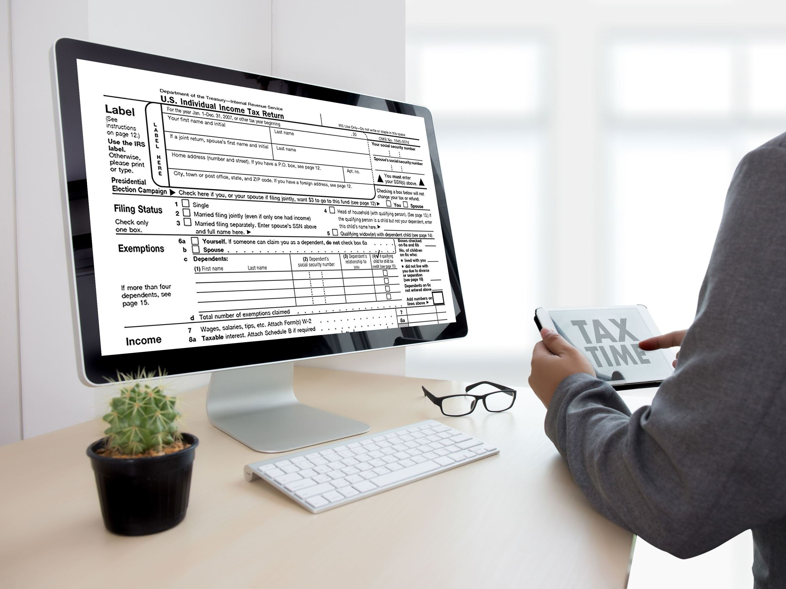 Accountant preparing income taxes using the computer.