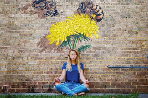 woman meditating in front of Bee Mural in Carrboro